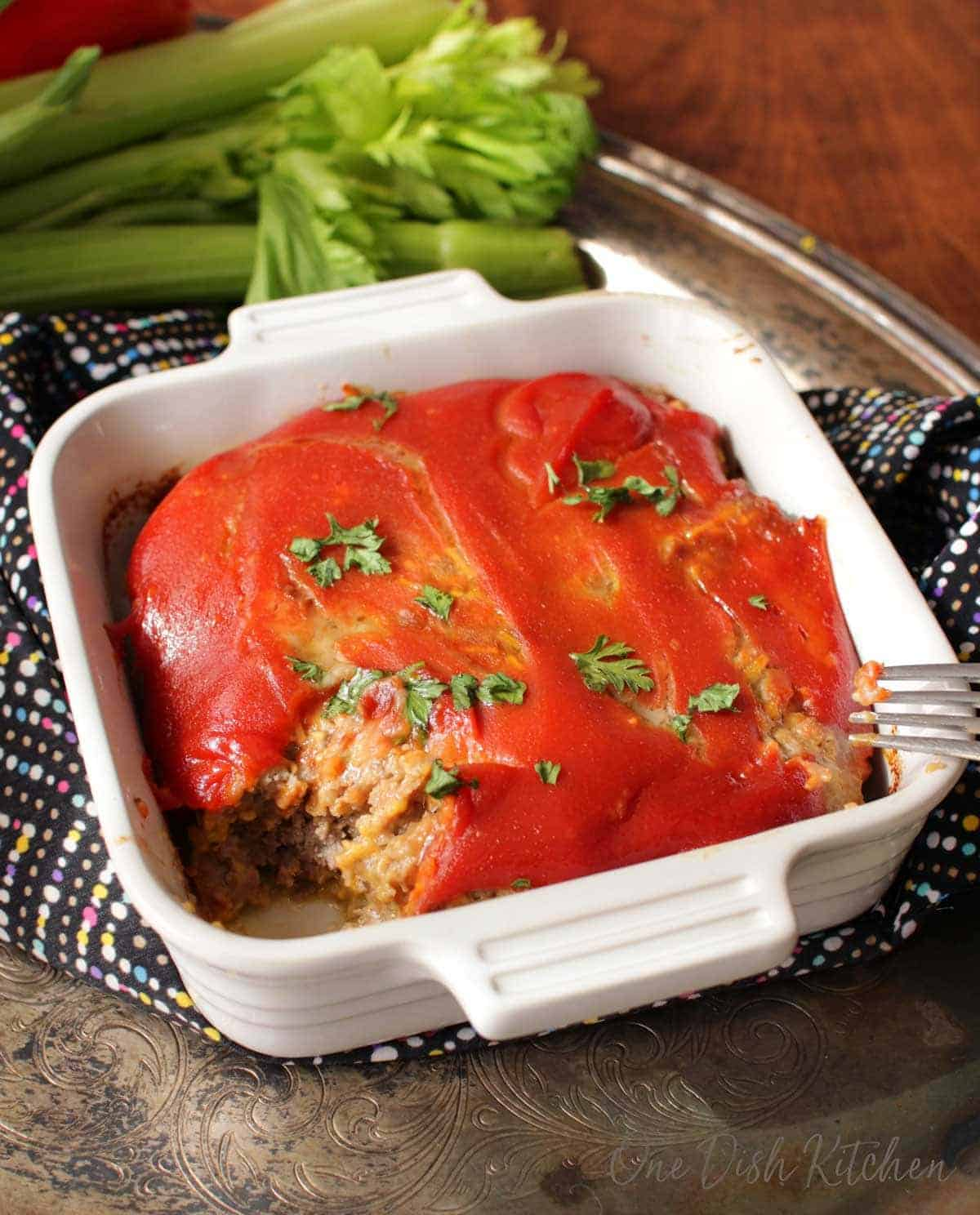 A forkful of bacon cheeseburger meatloaf missing from a small baking dish on a metal tray next to a bunch of celery