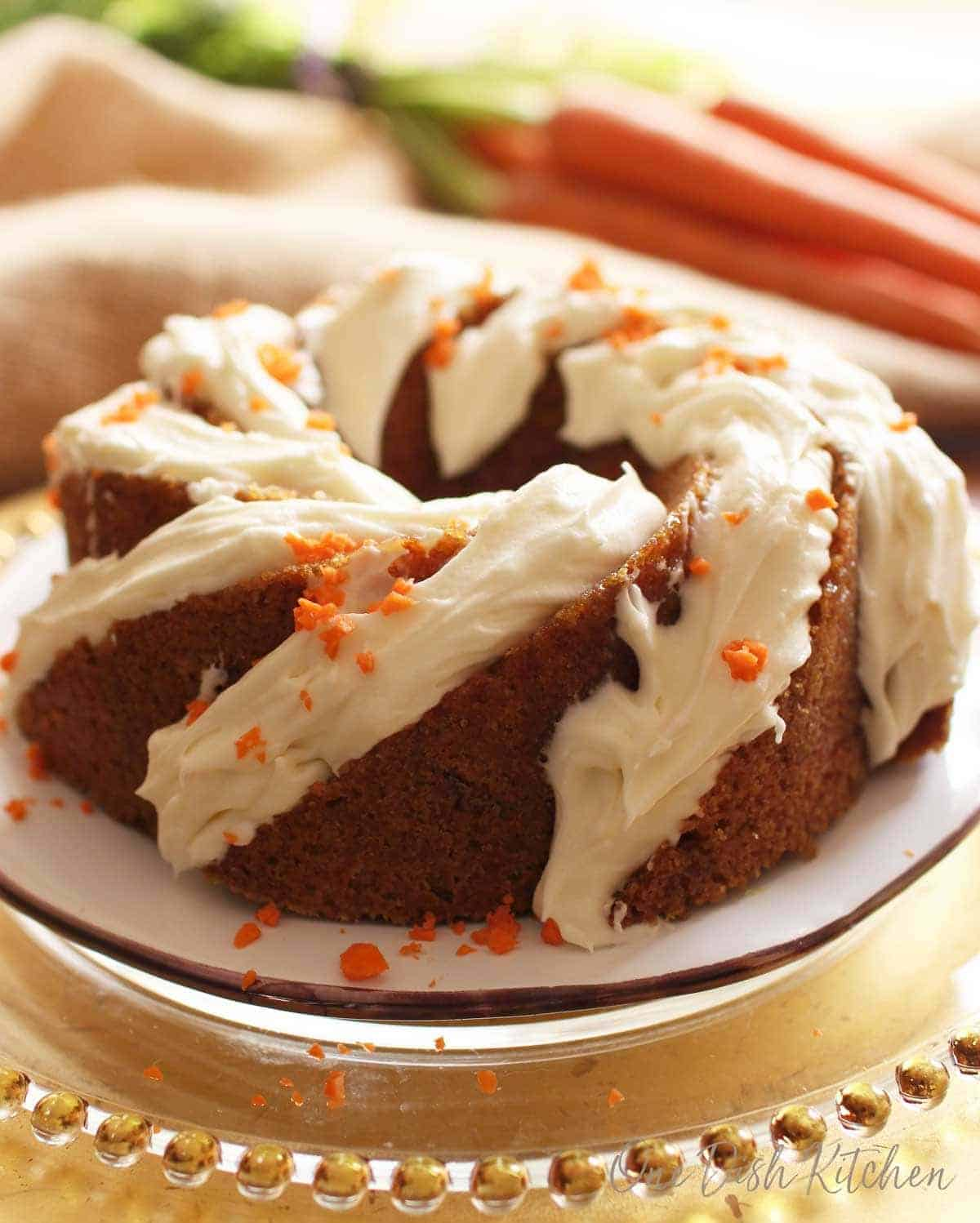 A frosted carrot bundt cake with bits of chopped carrots on top