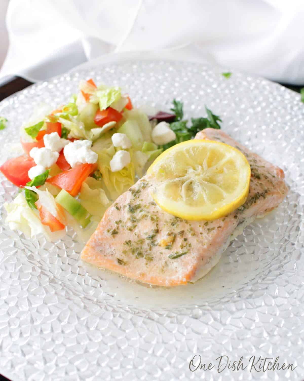 Baked salmon topped with a lemon wheel next to a side salad of iceberg lettuce, diced tomatoes and feta cheese all on a plate