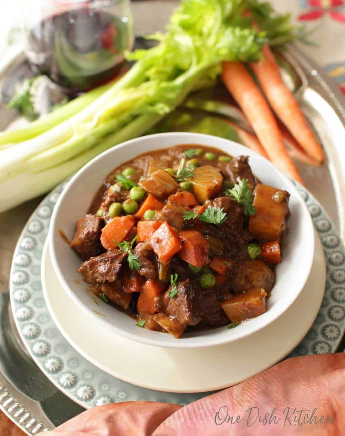 Overhead view of a bowl of beef stew next to two carrots, a stalk of celery, and a glass of red wine all on a metal tray