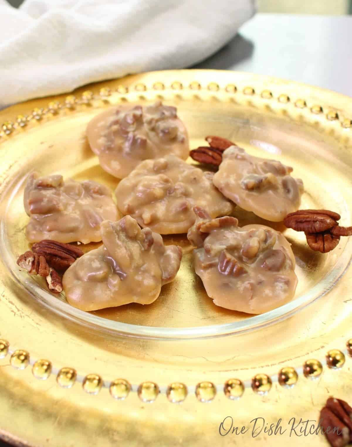 A gold plate with five pecan pralines on it.