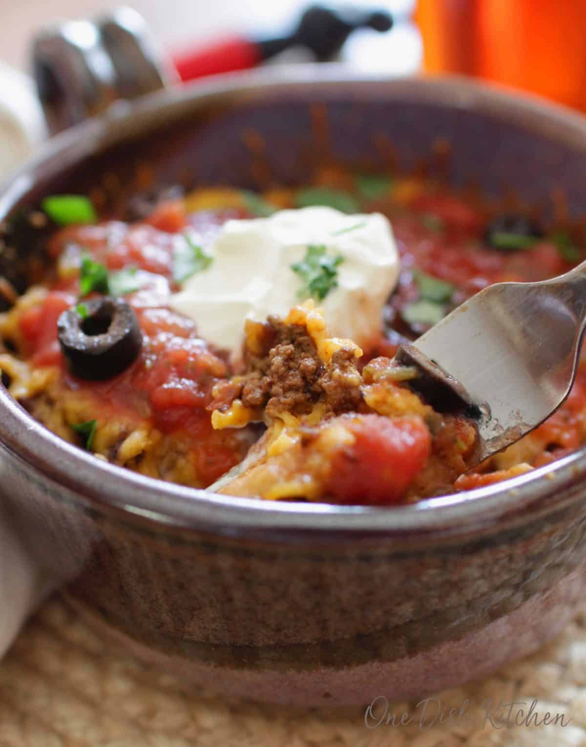 A fork filled with ground beef and cheese from the taco casserole in a circular dish