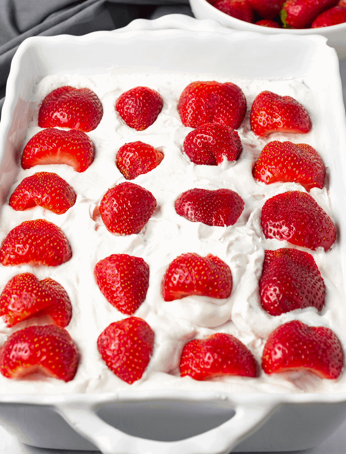 Gluten-Free Vegan strawberry ice-box cake overlay topped with strawberries in a white casserole dish