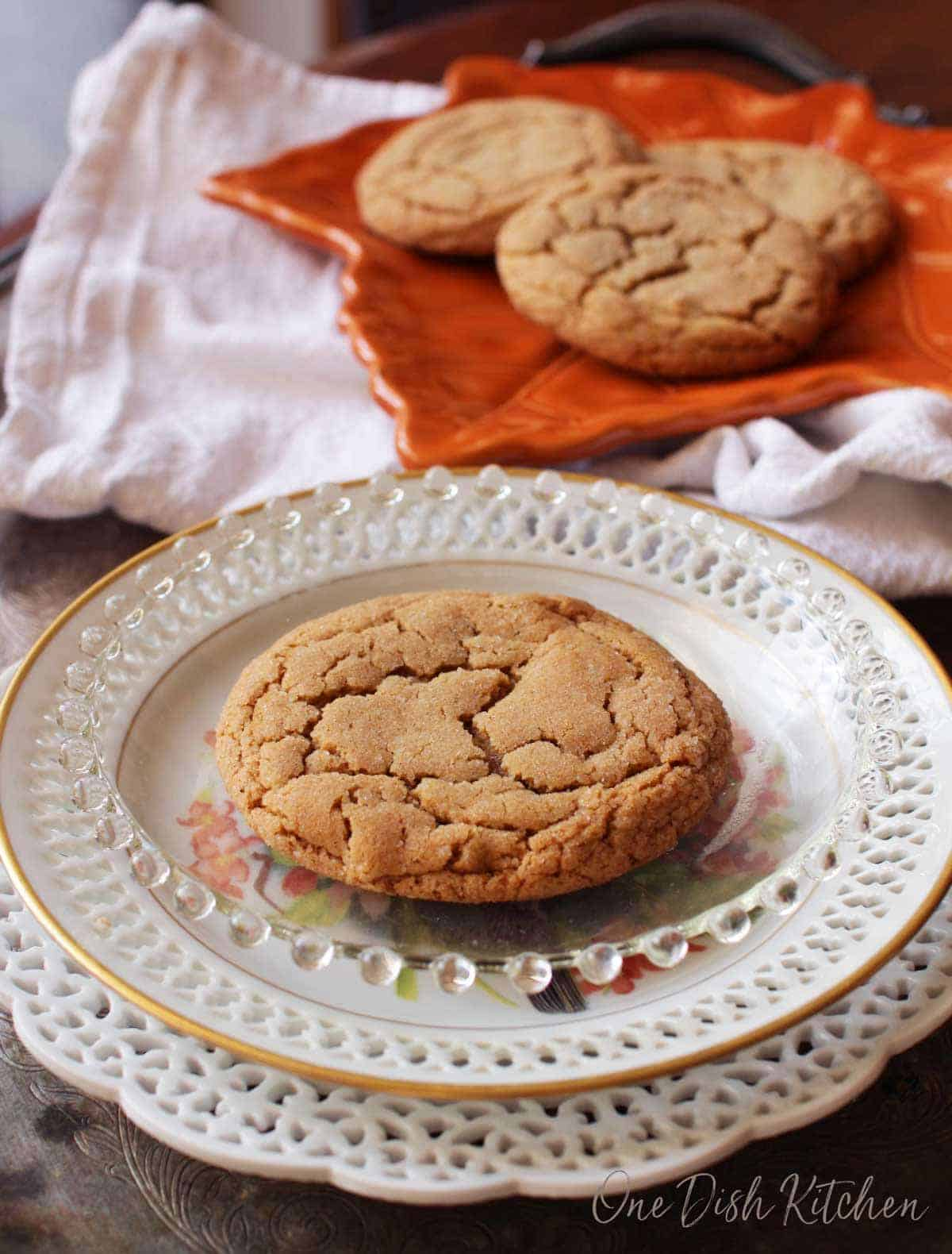 One ginger cookie on a plate with a platter of cookies on a tray in the background