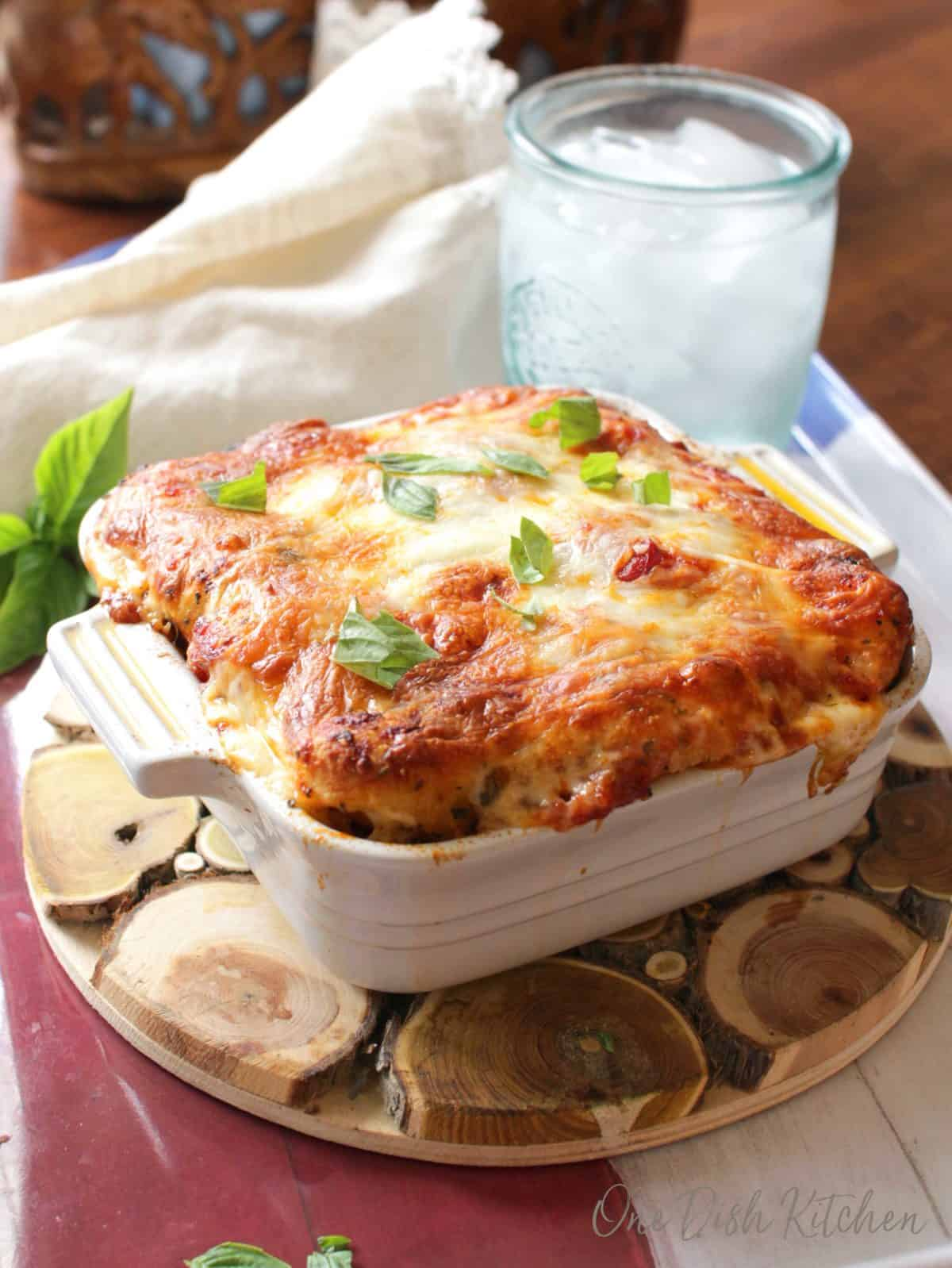 a white dish filled with balls of dough topped with mozzarella cheese.