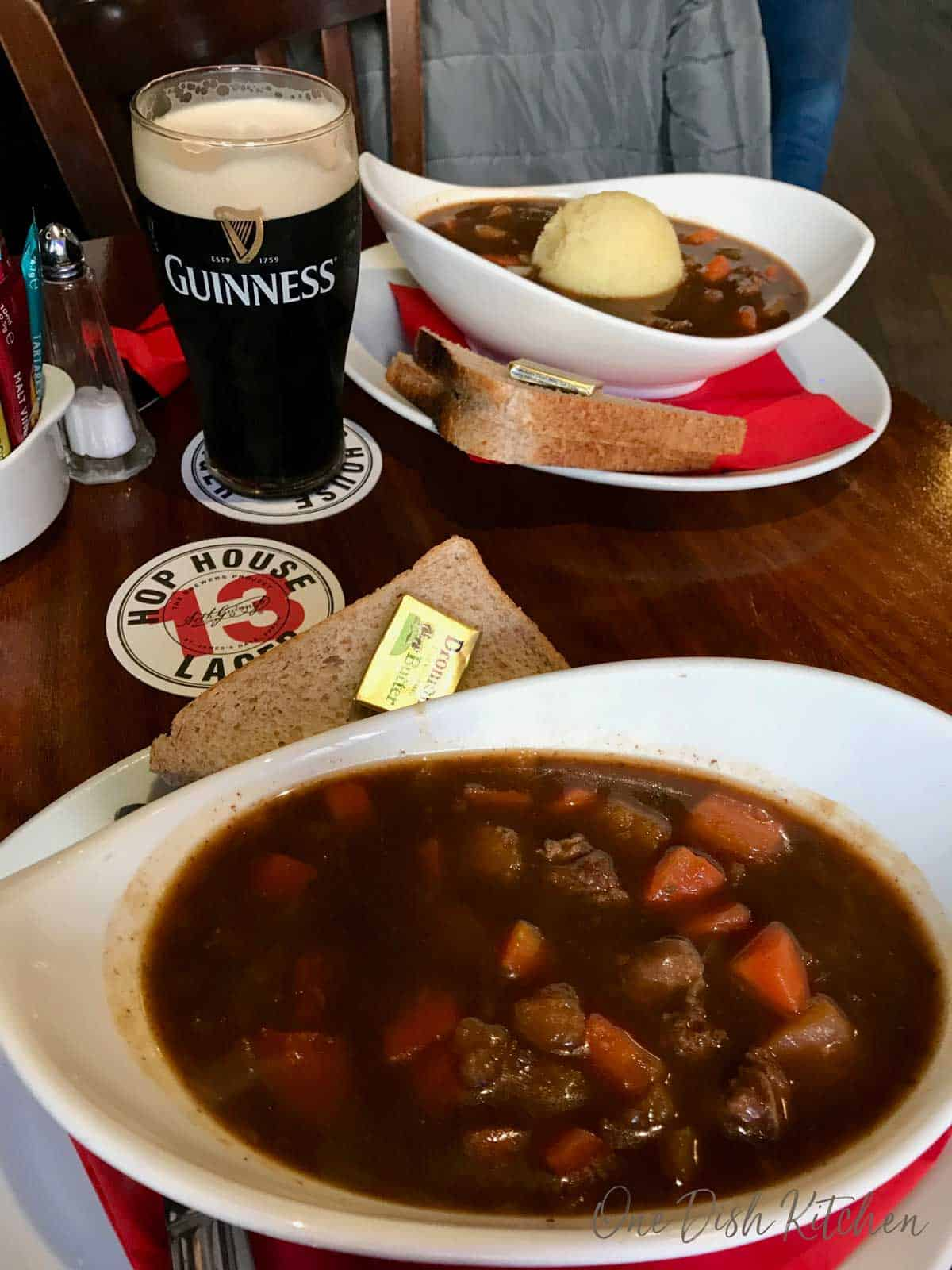Enjoying two bowls of irish stew in a pub in dublin with a glass of Guinness.