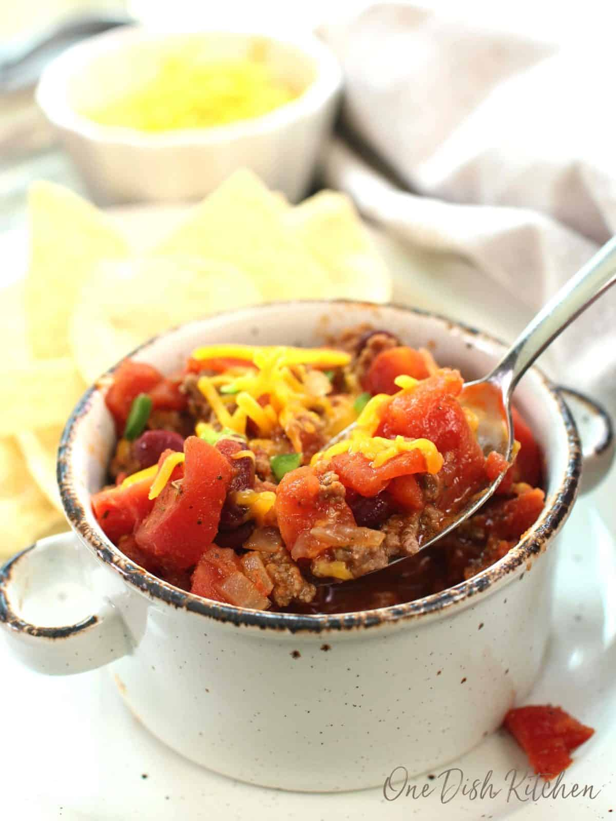 a spoon scooping up chili with tomatoes and shredded cheese.