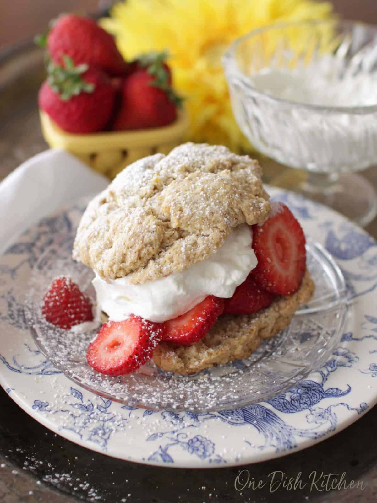 A strawberry shortcake filled with whipped cream and strawberries and dusted with powdered sugar on a plate with a bowl of whipped cream and a bowl of strawberries in the background.