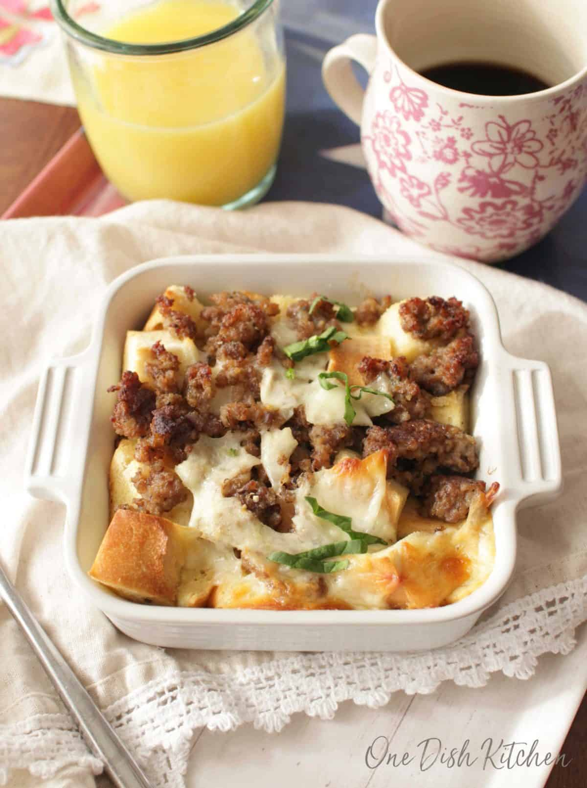 Breakfast casserole in a small baking dish next to a glass of orange juice and a coffee mug