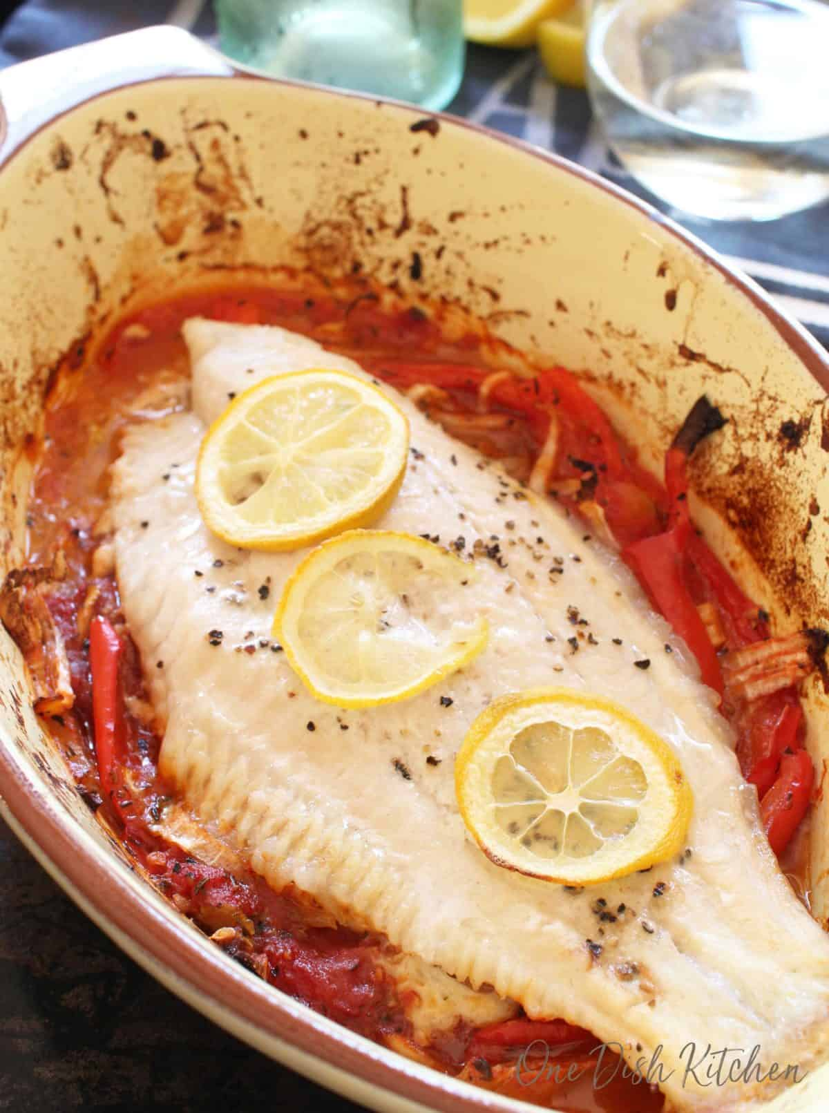 Closeup of catfish in a baking dish garnished with three lemon wheels and pepper flakes baked on a bed of red peppers and onions and there is a glass of white wine in the background.