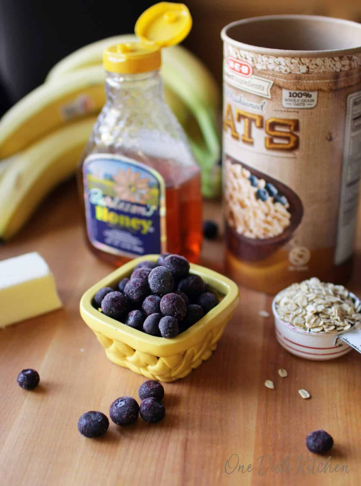 blueberries, bananas, oats, honey and butter on a brown cutting board.