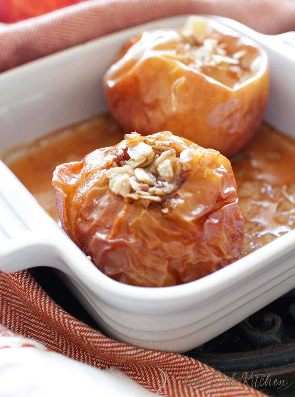 Two baked apples in a small baking dish filled with oats and brown sugar