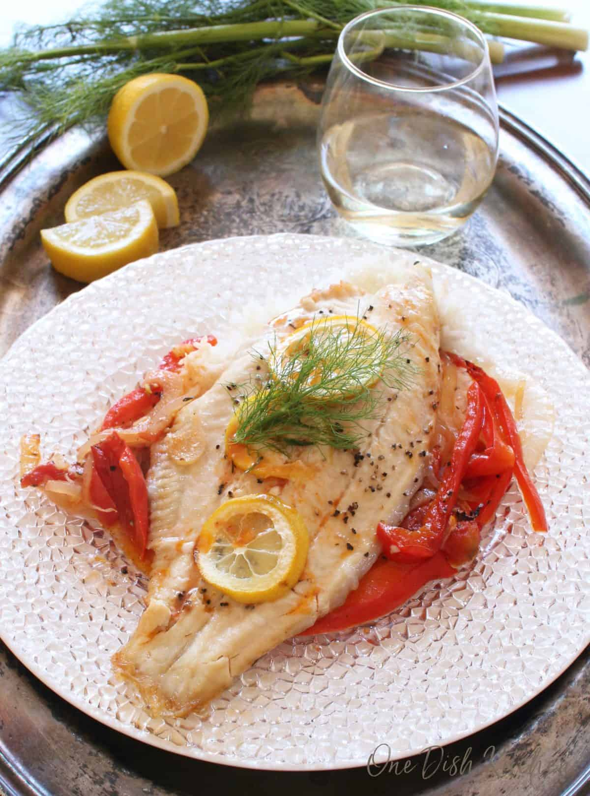 Baked catfish garnished with three lemon wheels over cooked white rice, red peppers, and onions on a glass plate on a metal tray with lemon slices and a glass of white wine