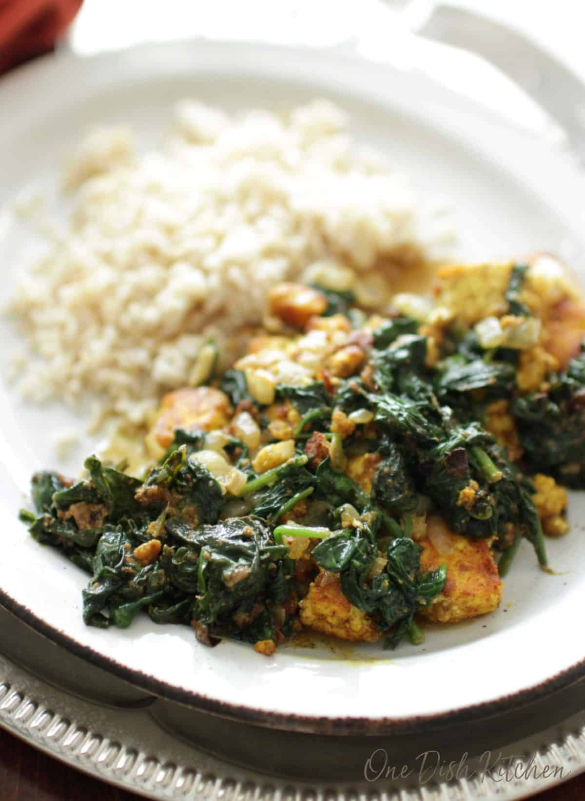 Spinach and cubes of paneer on a plate with white rice.