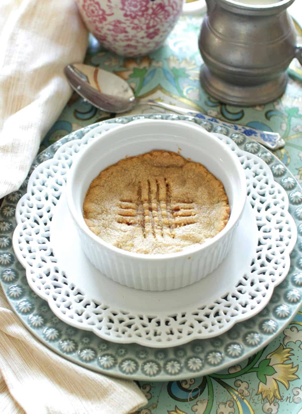 a cookie baked in a small white ramekin on a green plate,