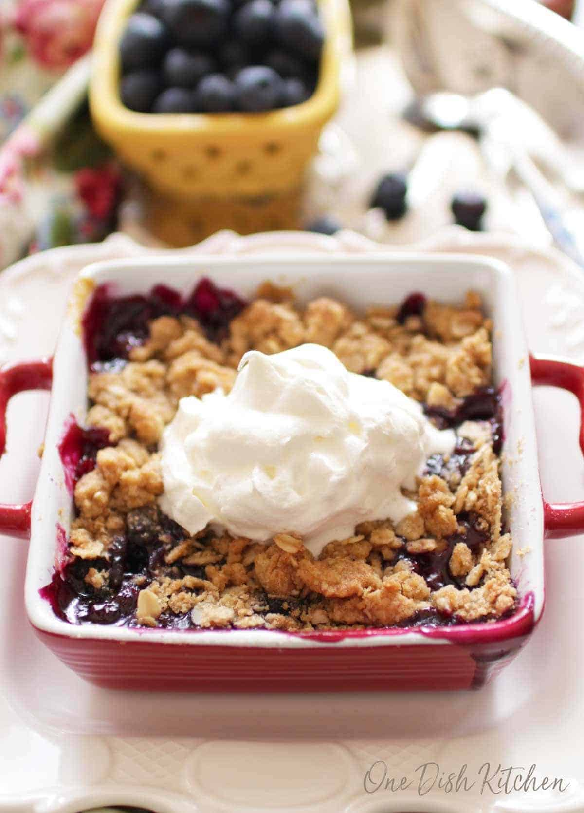 Mini blueberry crumble in a small red baking dish topped with whipped cream next to a small bowl of blueberries all on a metal tray