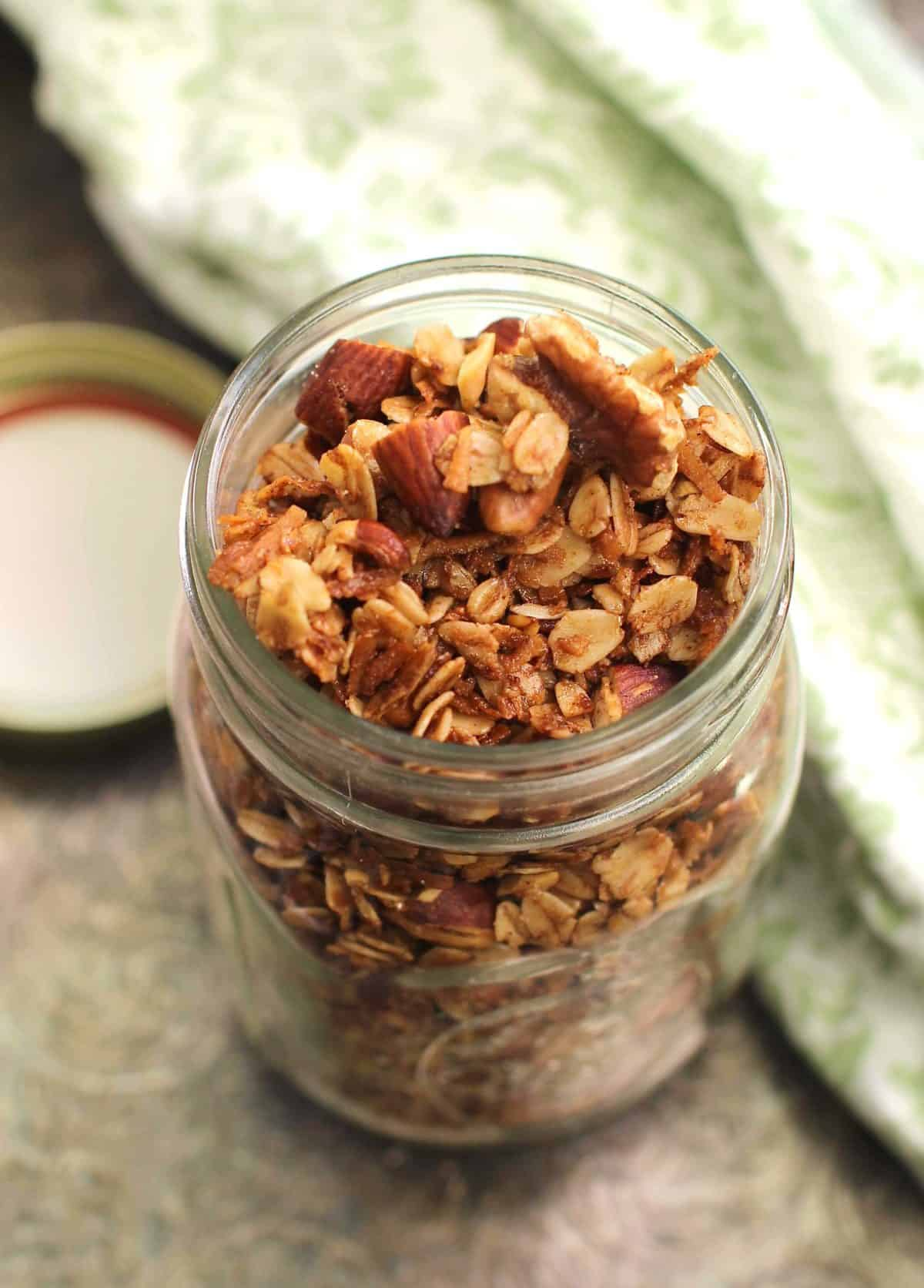 an overhead view of granola in a small mason jar next to a green and white napkin.