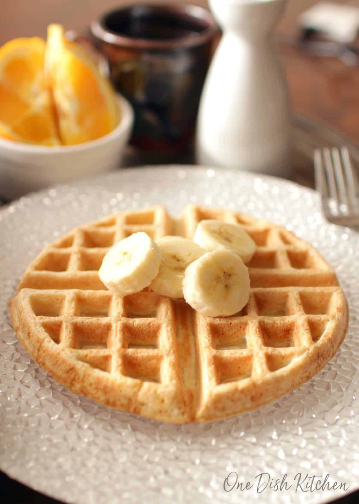A waffle topped with banana slices on a large plate with a mug of coffee and orange slices in the background