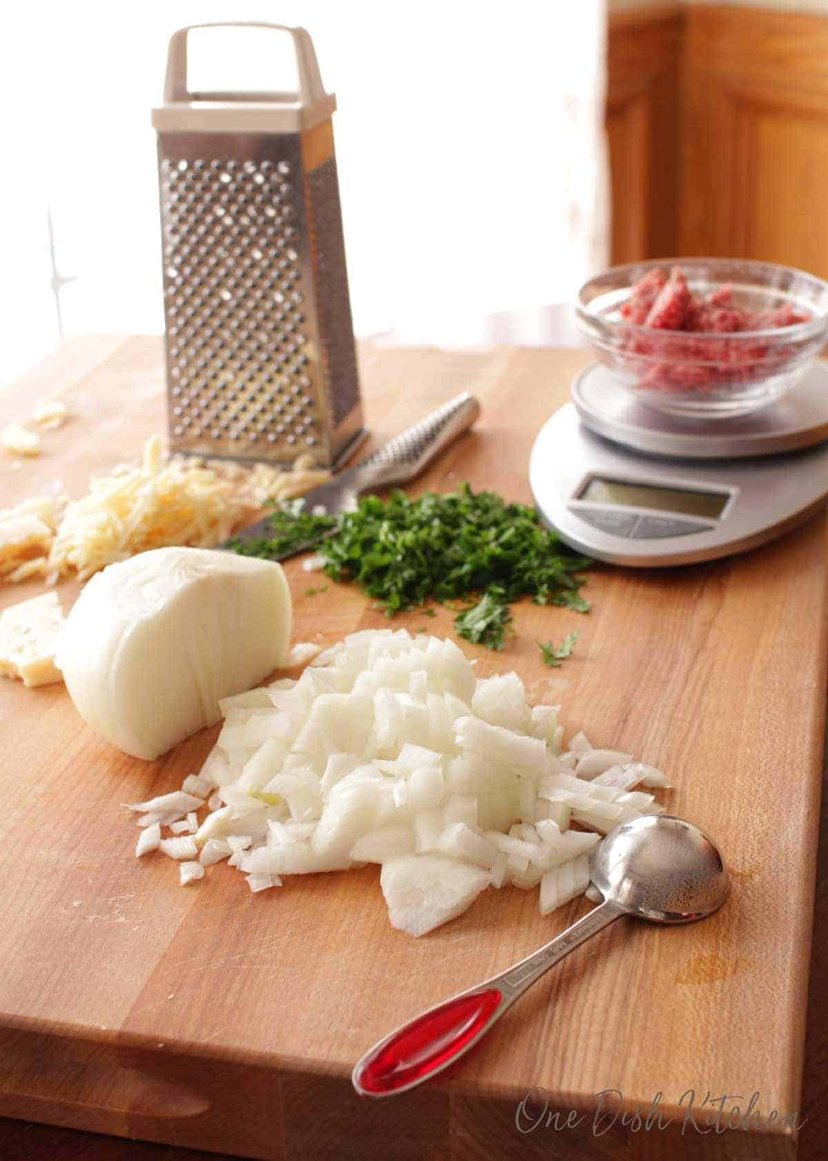 Ingredients for making a meatball on a wooden cutting board- chopped onions, chopped parsley, grated parmesan cheese, and ground beef on a scale