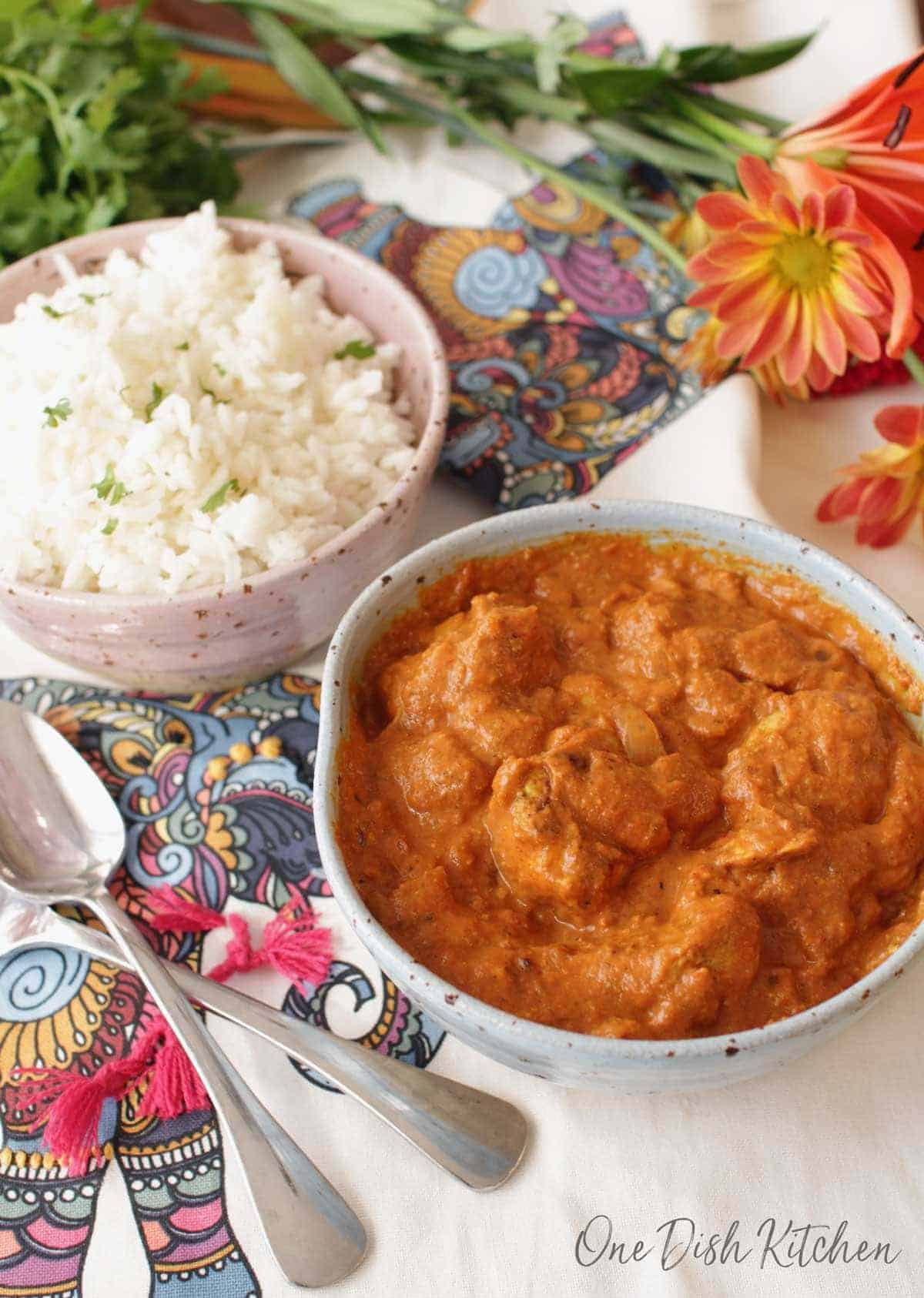 An overhead view of a bowl of butter chicken with a fork and a spoon next to another bowl of white rice