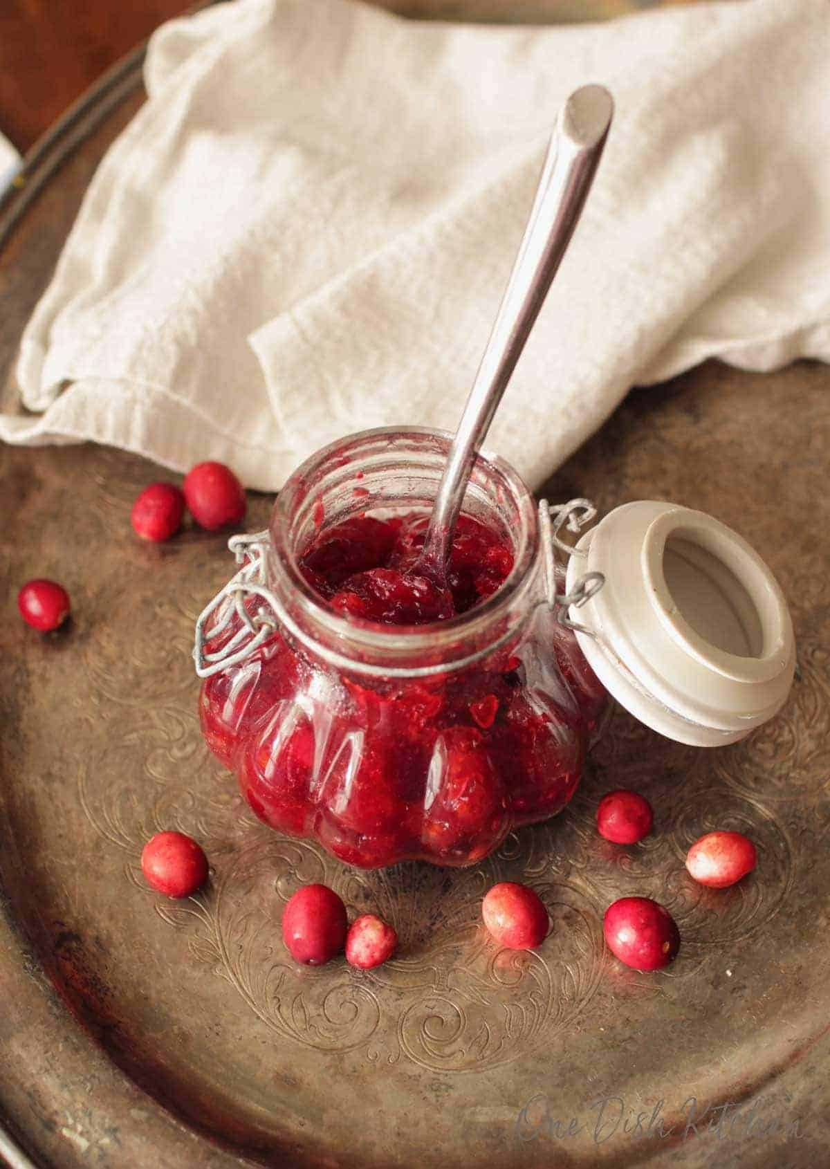 An overhead view of a jar of cranberry jam with a spoon on a metal tray with scattered cranberries and a white cloth napkin