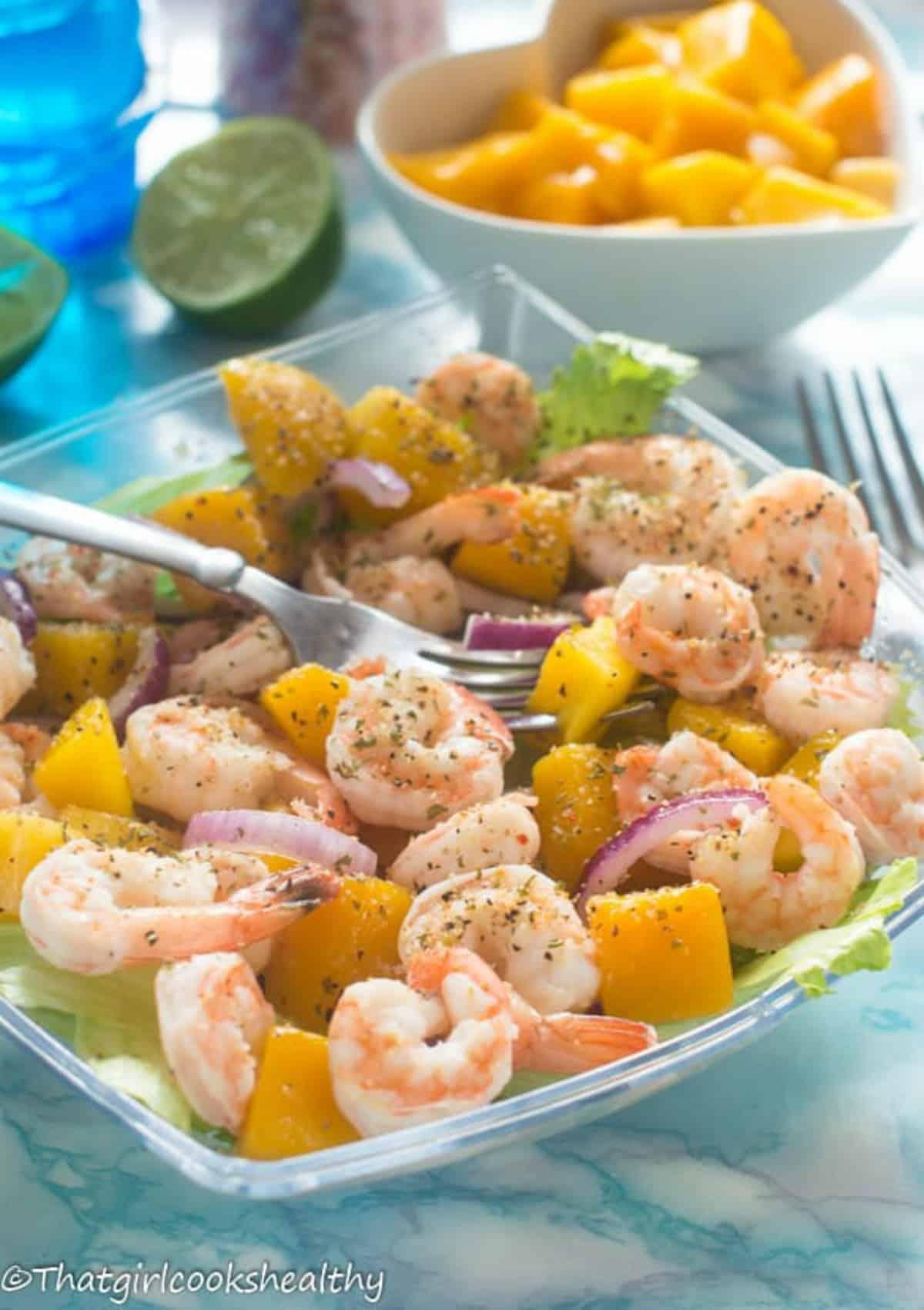 prawn, mango salad in a clear bowl