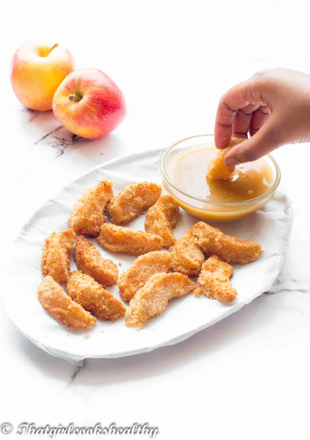 Dipping apple wedge into sauce