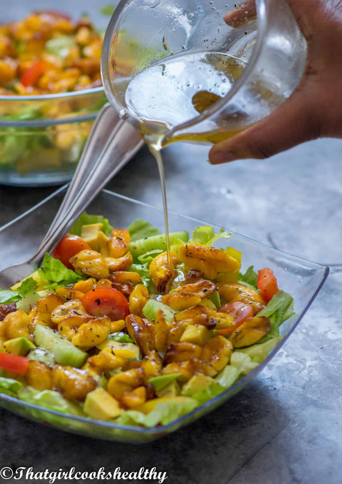 pouring dressing onto the salad