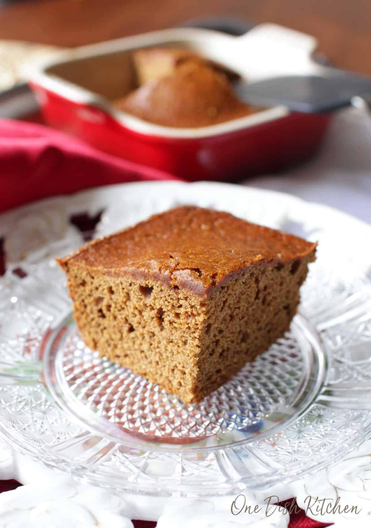 A square slice of gingerbread on a small plate with the baking dish in the background