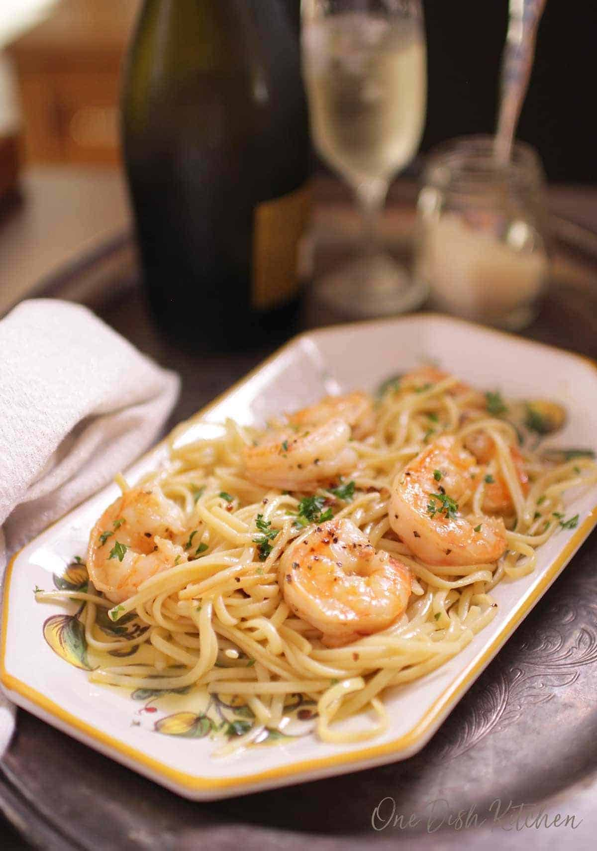 A plate of spaghetti with shrimp on a tray next to a small jar of parmesan cheese and a glass of champagne.