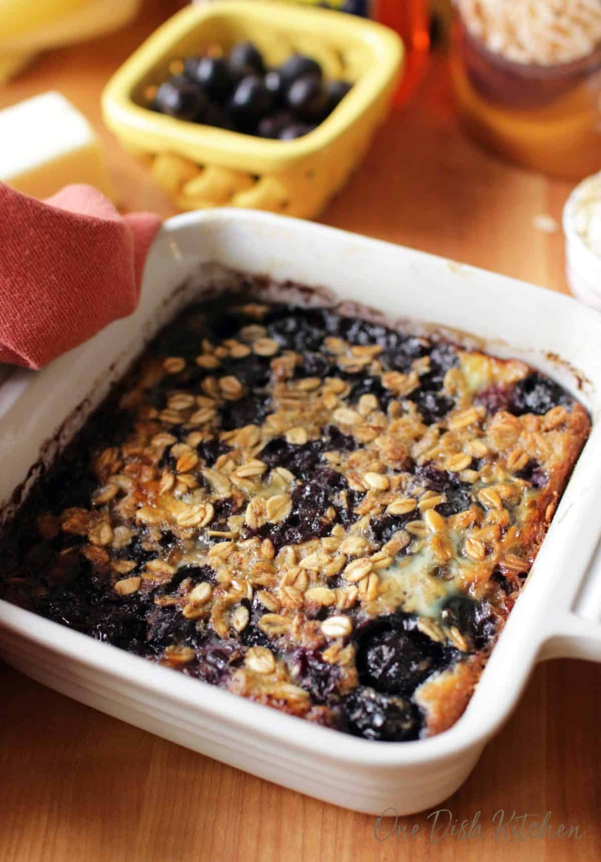 baked oatmeal with blueberries in a white square baking dish.