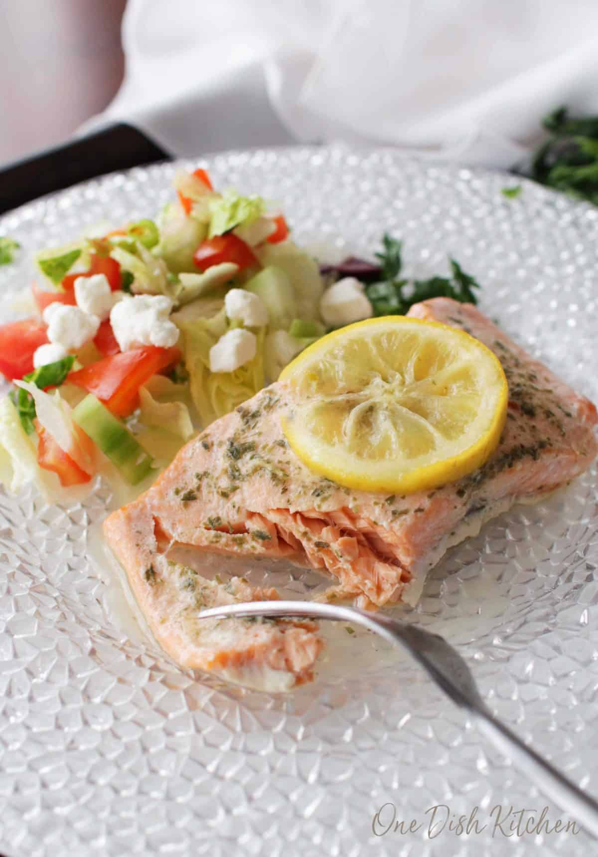 A forkful of Baked salmon topped with a lemon wheel next to a side salad of iceberg lettuce, diced tomatoes and feta cheese all on a plate