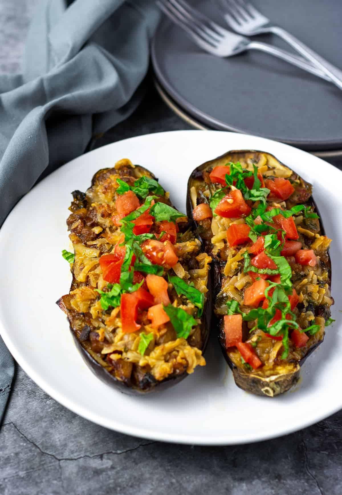 Vegan stuffed eggplant on a white plate, garni