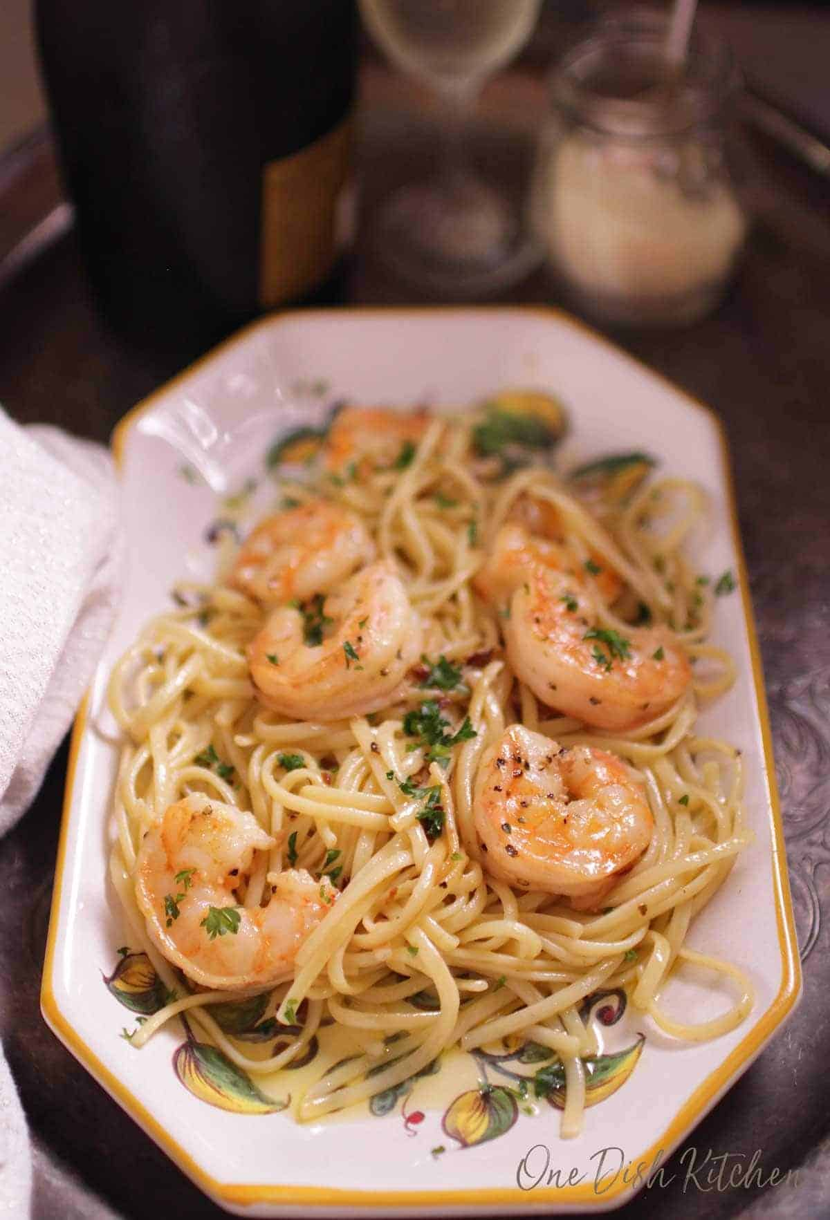 An overhead view of a plate of spaghetti with shrimp on a tray next to a small jar of parmesan cheese and a glass of champagne.