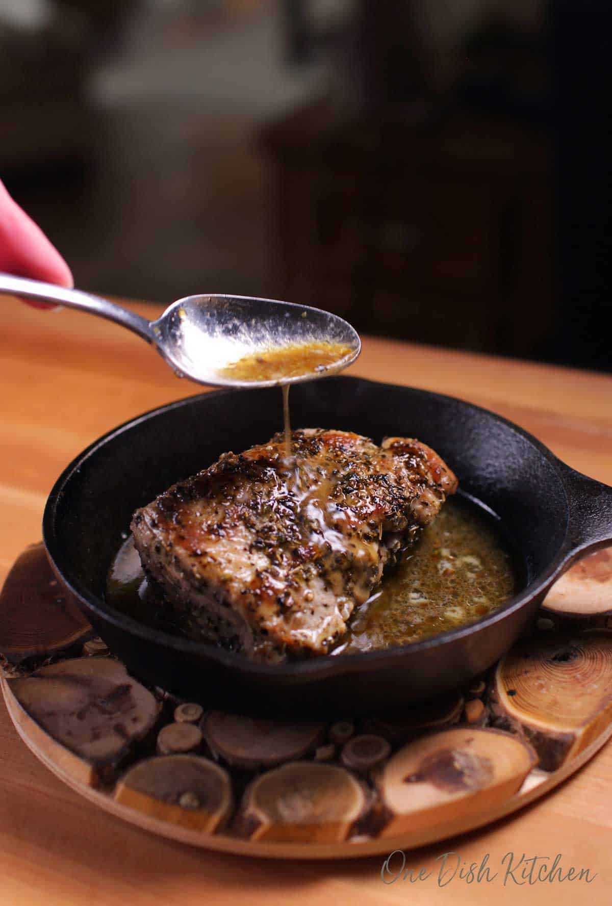 A spoon pouring gravy onto a pork tenderloin in a cast iron skillet on a wooden trivet