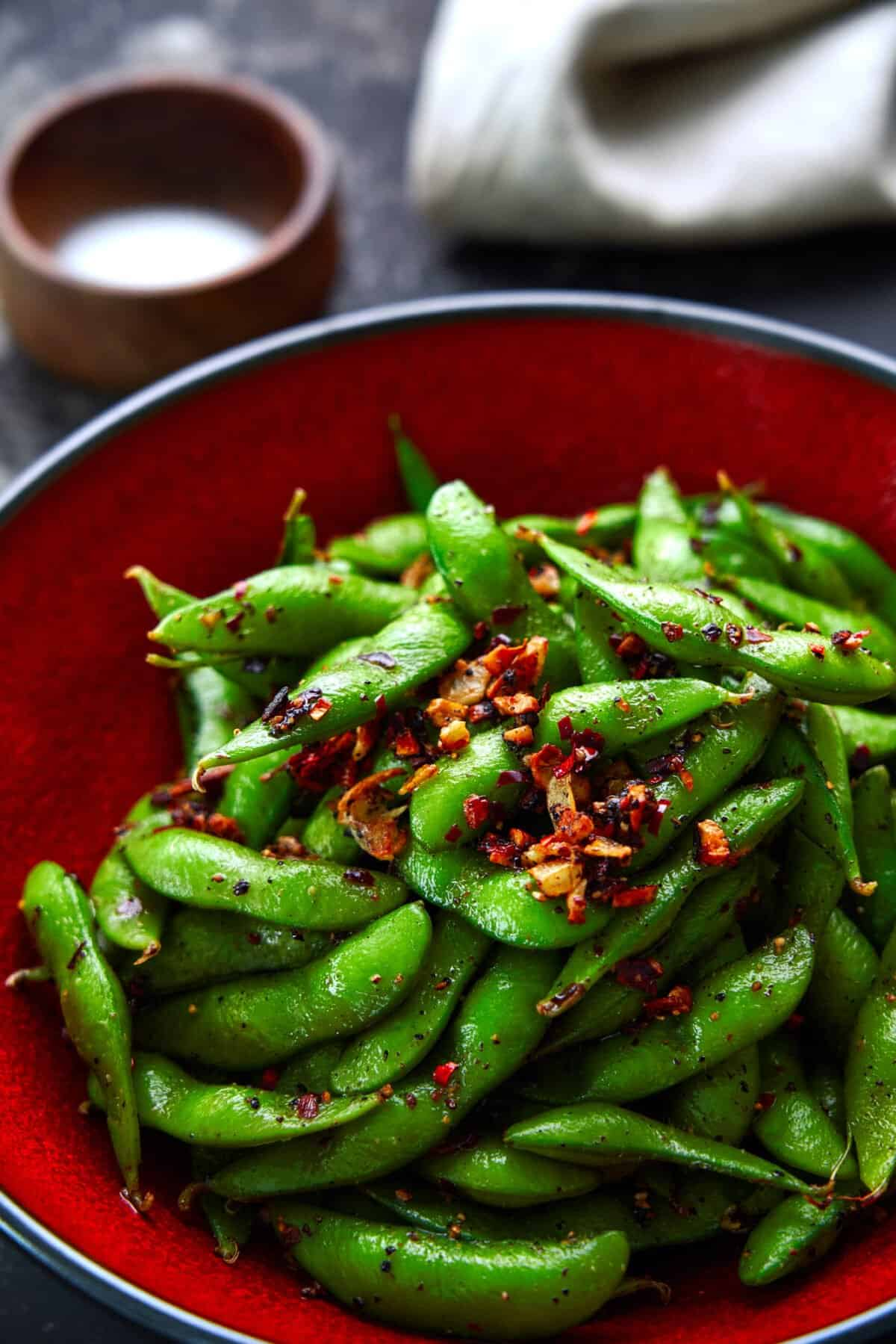 Up your snack game with this Spicy Edamame recipe that's loaded crispy garlic and a double hit of black pepper and chili peppers.