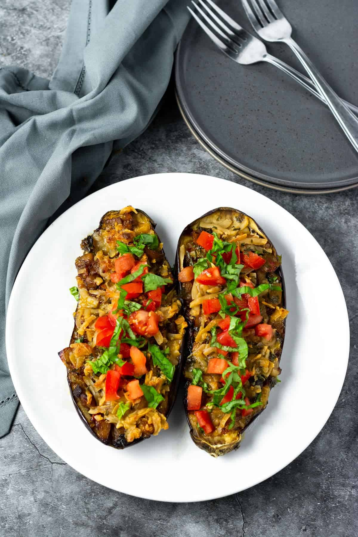 Vegan stuffed eggplant on a white plate with grey napkin, 2 forks on a grey background