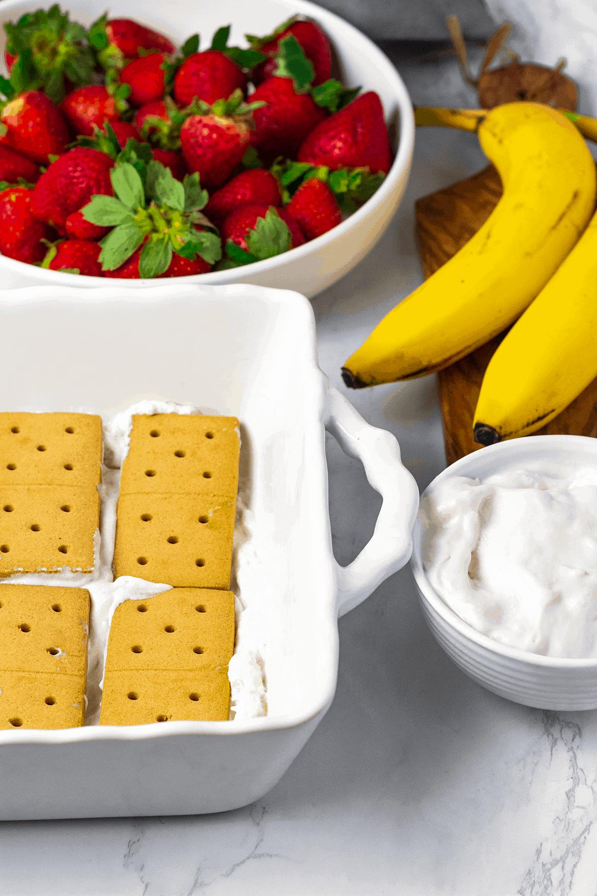 Vegan strawberry ice box cake ingredients, Graham crackers, whipped cream, banana, strawberry