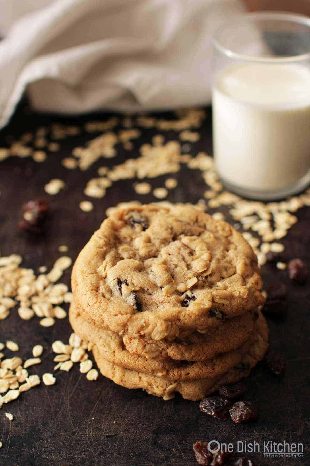 A stack of four oatmeal cookies on a dark surface with scattered oats and raisins and a glass of milk in the background