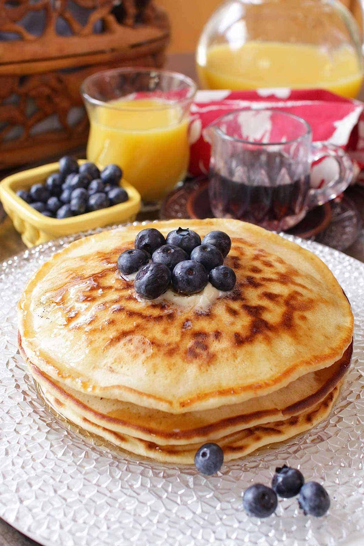 Three pancakes stacked on a plate and topped with melted butter and blueberries next to a small bowl of blueberries, a glass of orange juice, and a small glass container of maple syrup