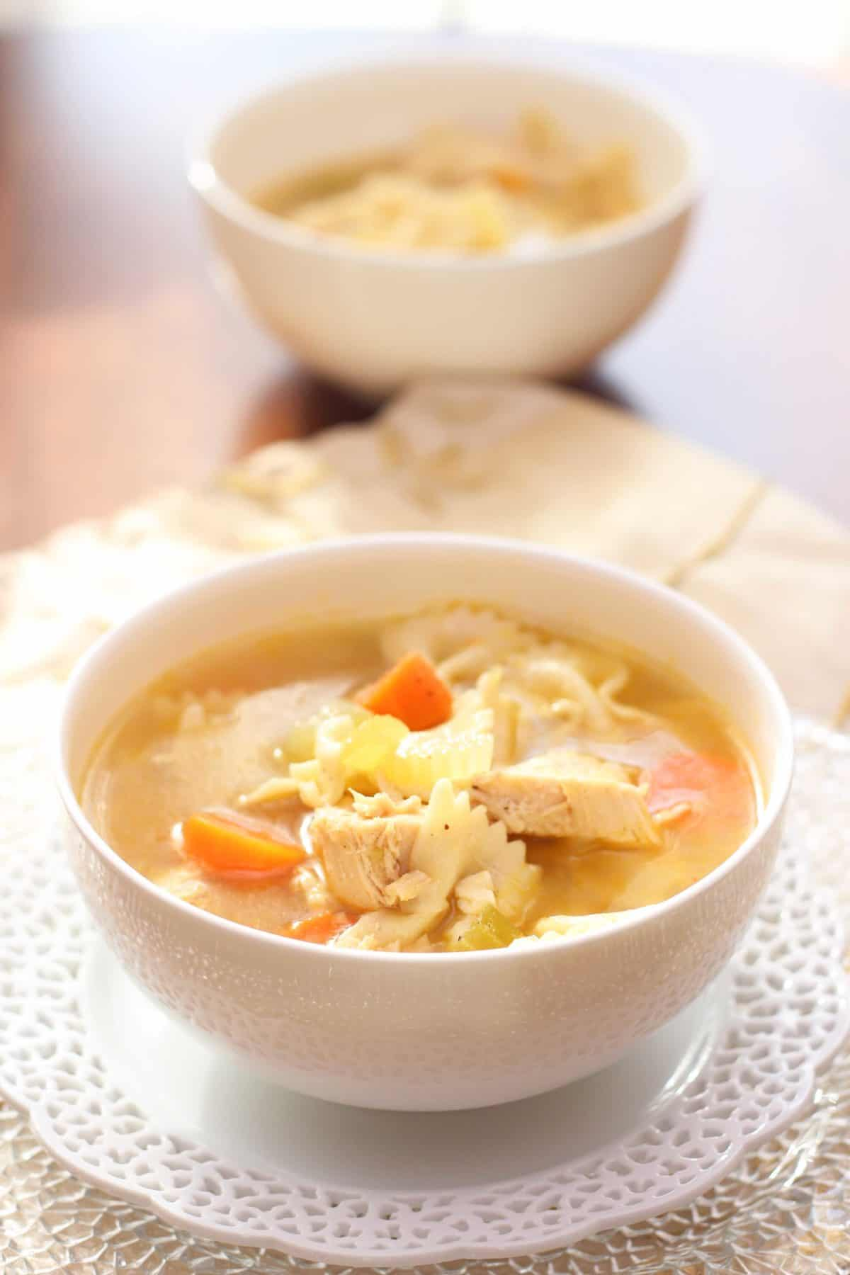 a bowl of chicken soup on a white lace plate.
