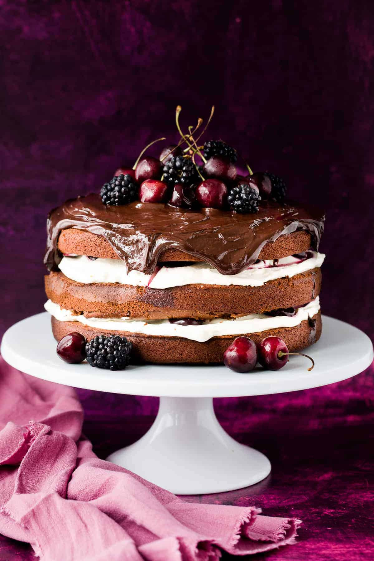 A 3 layer black forest cake made from chocolate sponge with a cream and cherry layer and dark chocolate ganache on top.