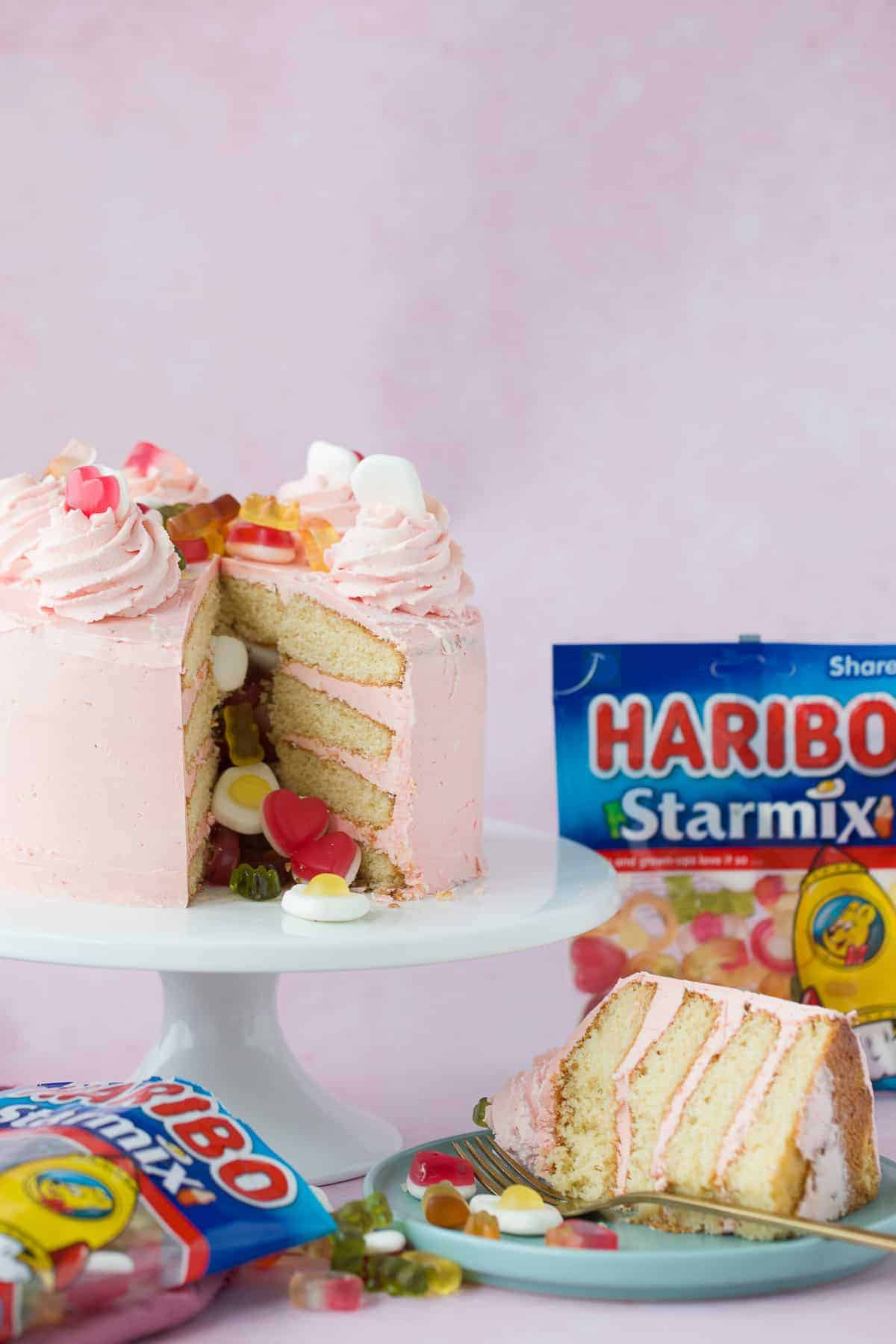 A layer cake on a pink platter with a slice cut out from it and a bag of HARIBO sweets in the background.