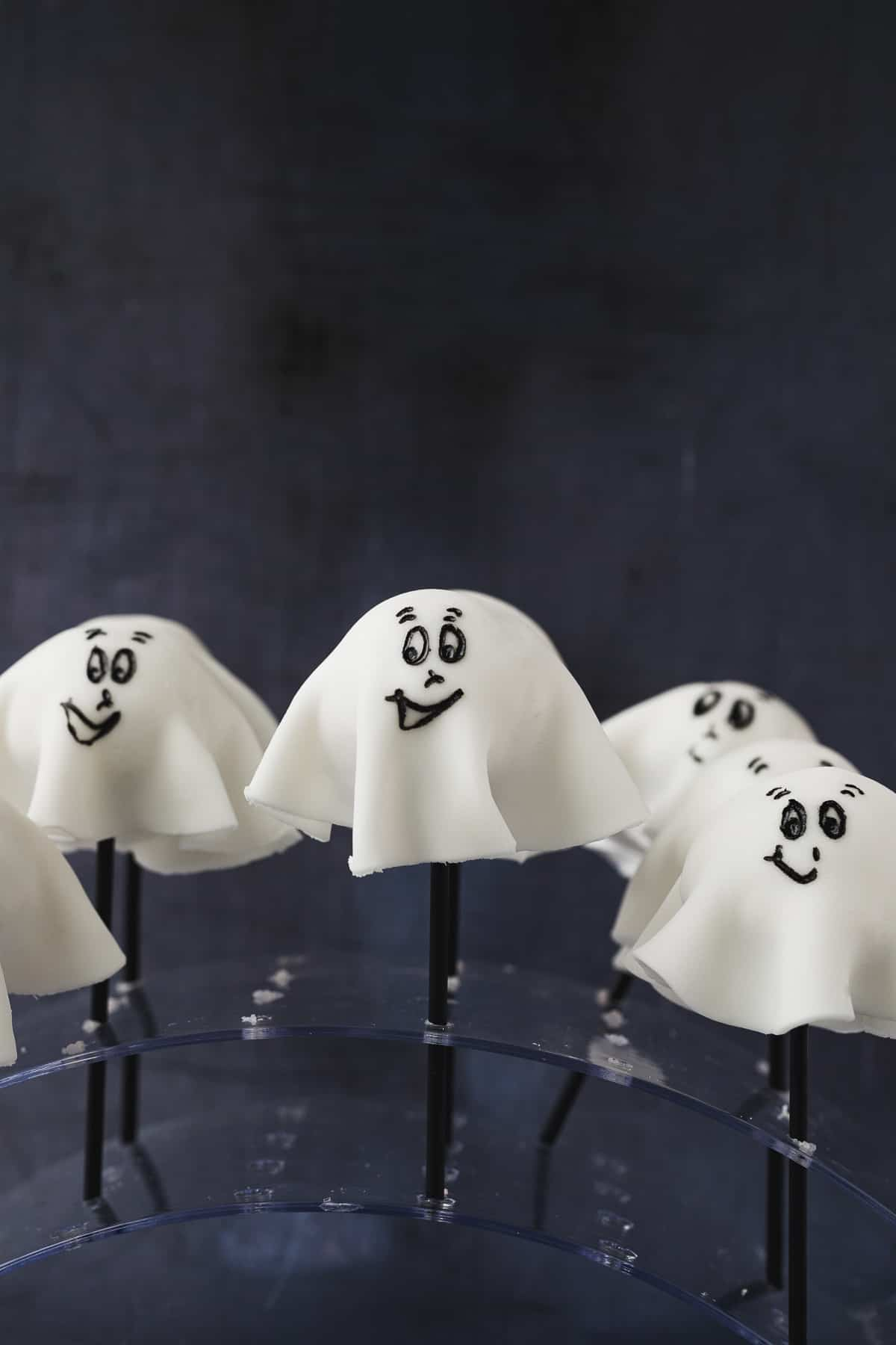 Chocolate cake pops covered in white fondant icing with a face drawn on to look like a friendly ghost.