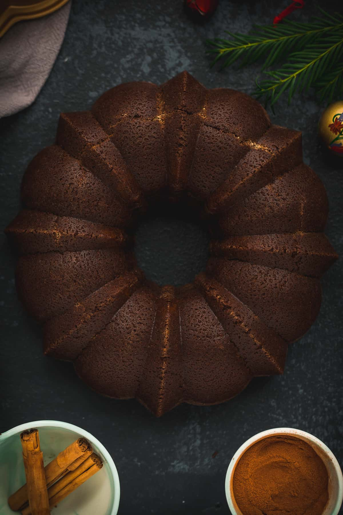A ginger cake on a very dark background. There is a bowl of ground ginger next to it and another bowl with cinnamon sticks.