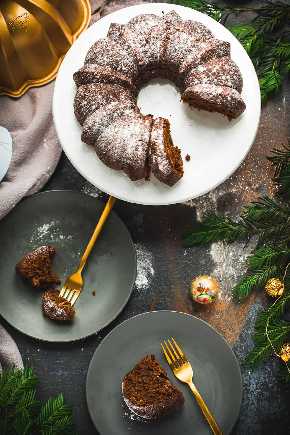 Overhead view of a bundt cake on a white platter. Two pieces have been cut out and they have been placed onto dark grey plates with gold coloured forks. The scene is surrounded by Christmas decorations and looks very festive.