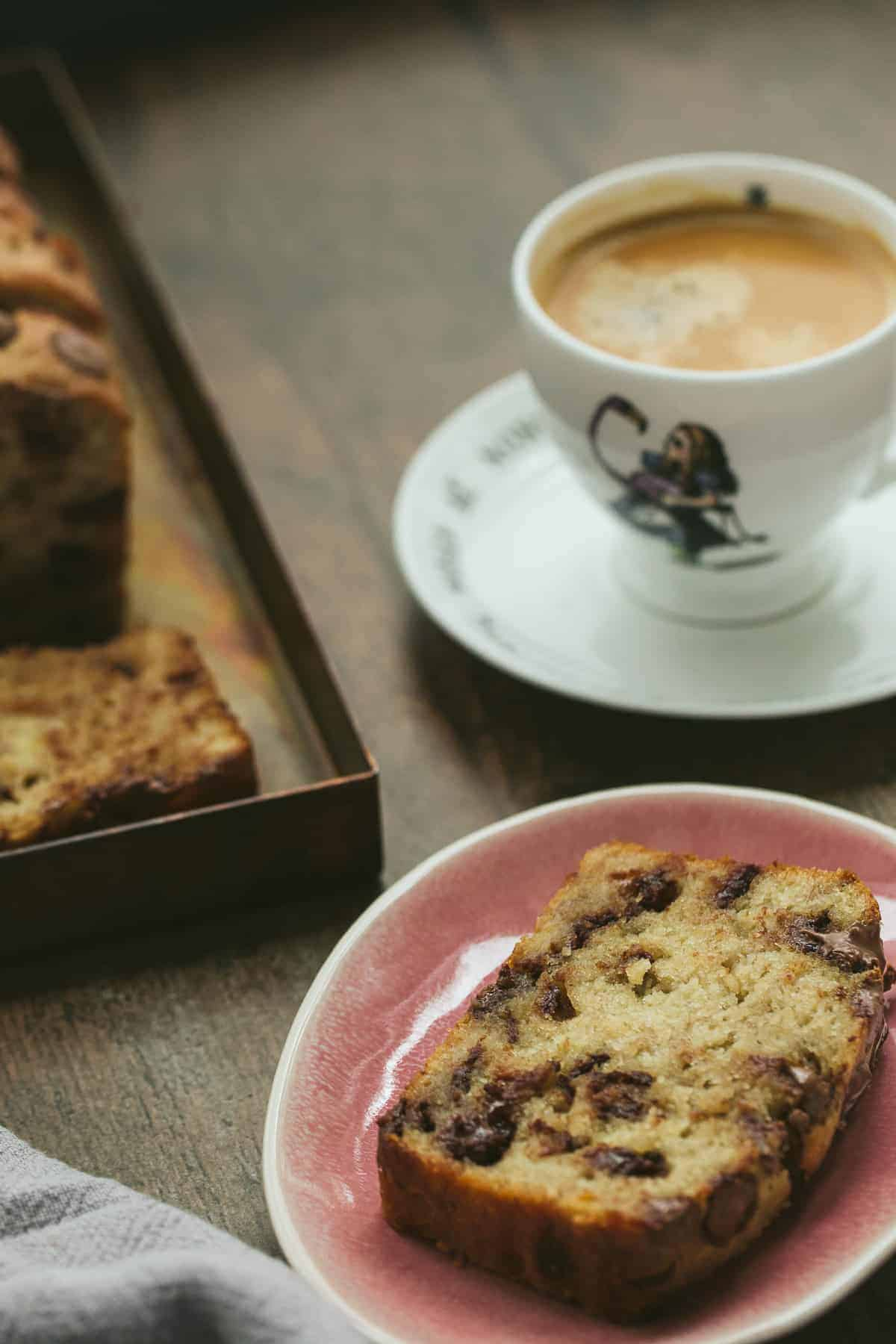 A slice of banana loaf on a pink plate. The slice has chocolate chips inside the bread. There is a cup of coffee in a decorative cup in the background.