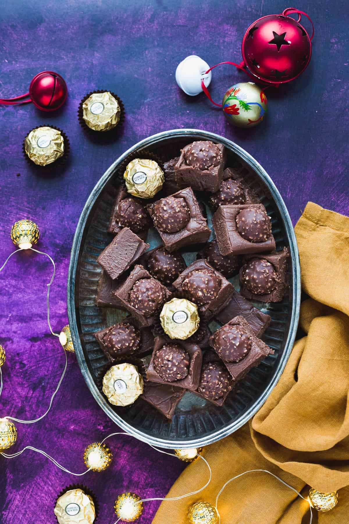 Chocolate fudge on a platter. There is a dark purple background and the platter is surrounded with Christmas decorations.
