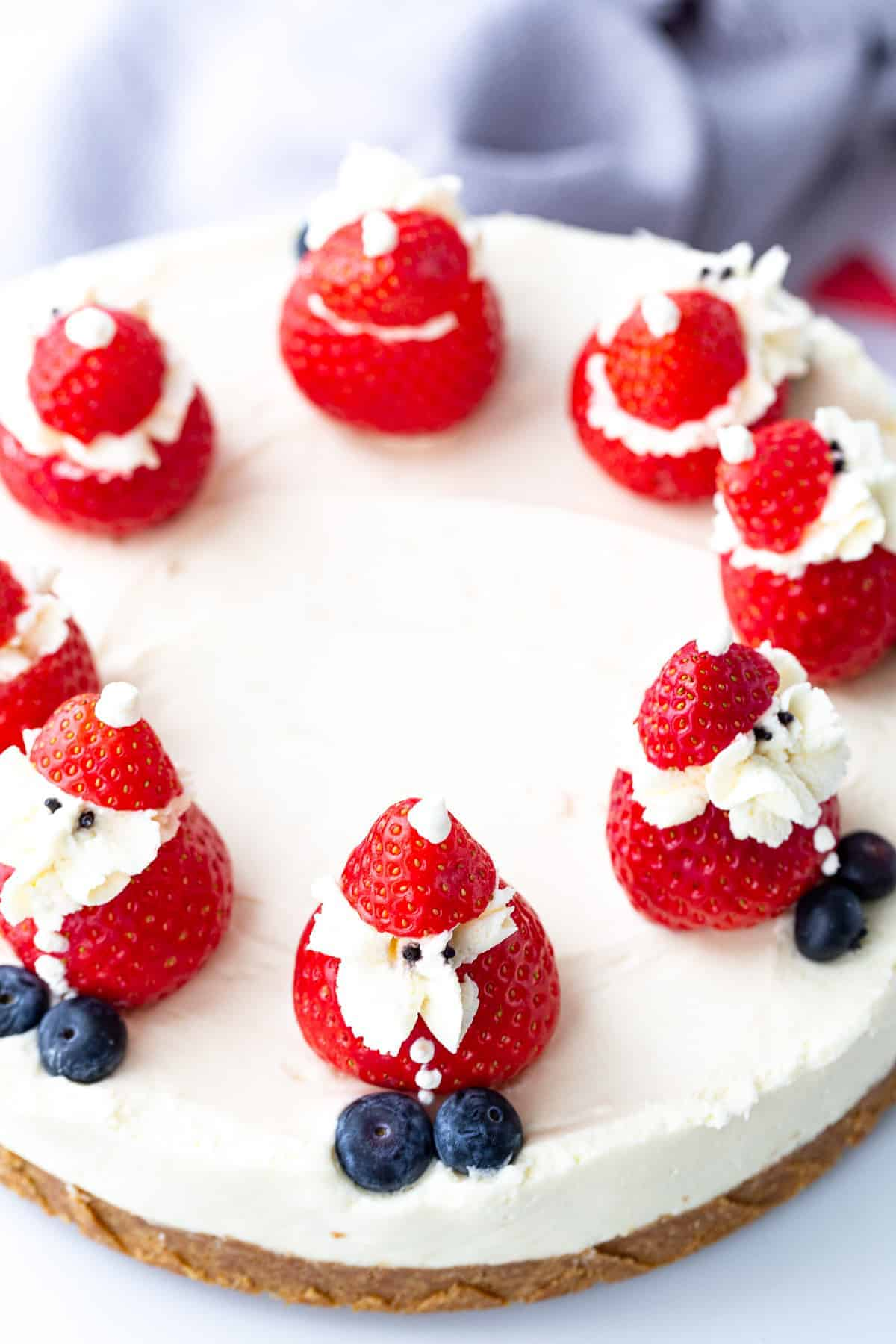 A no-bake white chocolate cheesecake with stuffed strawberry santas.