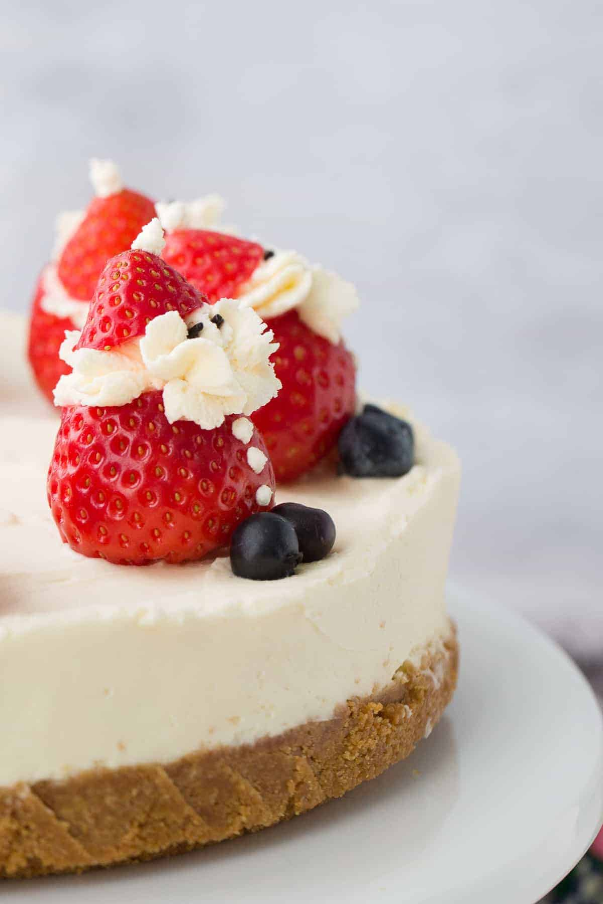 Side profile of a white cheesecake with a biscuit base. There are stuffed strawberries on top.